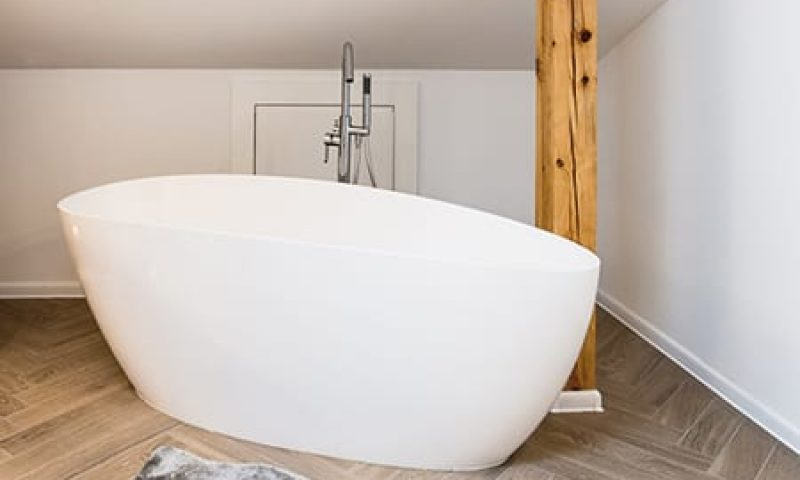 Oval bathtub and toilet in minimalist, bright, white bathroom interior